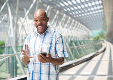 With gadget. Copy-spaced portrait of a cheerful black businessman with a gadget in hands stock images