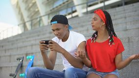 Gadget-addicted boyfriend ignoring his girlfriend playing games on smartphone. Stock footage stock video