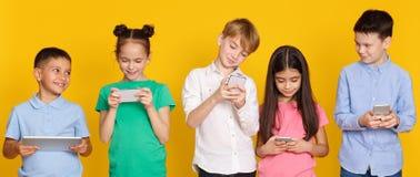Gadget addiction. Children with modern gadgets, yellow background. Gadget addiction. Children with modern gadgets standing over yellow background royalty free stock photo