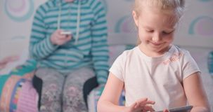 Gadget addiction. Cute little girl plays on the tablet, her mother sits on the bed playing in the smartphone stock footage