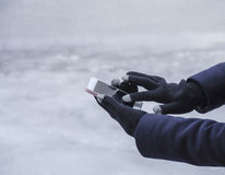Gadget in the hands of a girl in winter Stock Photo