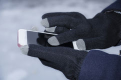 Gadget in the hands of a girl in winter Stock Photos
