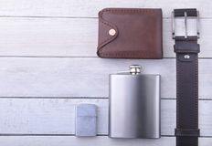 Gadgets and accessories for men on light wooden background. Fashionable men s belt, wallet, lighter, Stainless hip flask. And pen Royalty Free Stock Photography