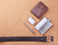 Gadgets and accessories for men on light wooden background. Fashionable men s belt, wallet, lighter, Stainless hip flask. And pen Royalty Free Stock Photos