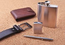 Gadgets and accessories for men on light wooden background. Fashionable men s belt, wallet, lighter, Stainless hip flask. And pen Royalty Free Stock Photo