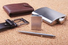 Gadgets and accessories for men on light wooden background. Fashionable men s belt, wallet, lighter, Stainless hip flask. And pen Stock Photography