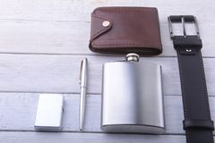 Gadgets and accessories for men on light wooden background. Fashionable men s belt, wallet, lighter, Stainless hip flask. And pen Royalty Free Stock Image