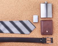 Gadgets and accessories for men on light wooden background. Fashionable men s belt, wallet, lighter, Stainless hip flask. And pen Royalty Free Stock Images