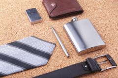 Gadgets and accessories for men on light wooden background. Fashionable men s belt, wallet, lighter, Stainless hip flask. And pen Stock Image