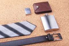 Gadgets and accessories for men on light wooden background. Fashionable men s belt, wallet, lighter, Stainless hip flask. And pen Stock Photo