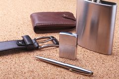 Gadgets and accessories for men on light wooden background. Fashionable men s belt, wallet, lighter, Stainless hip flask. And pen stock images