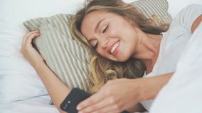 Gadgets in bed: girl uses a mobile phone at bedtime. She lies on side. Young woman in her bed using a smartphone and smiling. Gadgets in bed: a girl uses a stock footage