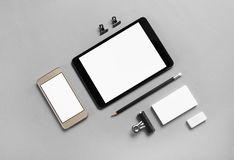 Blank stationery, gadgets. Gadgets with blank screens and stationery on gray paper background. Template for placing your design. Top view Stock Images