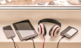 Gadgets on charging lying on the window. Several devices are charging. Headphones, tablet and phones.n Royalty Free Stock Photos