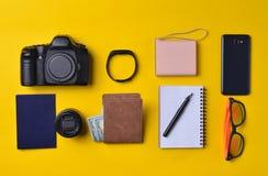 Gadgets en toebehorenlay-out op een gele achtergrond Machtsbank, fotografisch materiaal, beurs met dollars, slimme klok royalty-vrije stock foto's