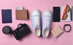 Gadgets en toebehorenlay-out op een roze pastelkleurachtergrond Tennisschoenen, fotografisch materiaal, beurs met dollars, slimme royalty-vrije stock foto's