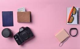 Gadgets en toebehorenlay-out op roze pastelkleurachtergrond Fotografisch materiaal, beurs met dollars, slimme klok, smartphone stock fotografie