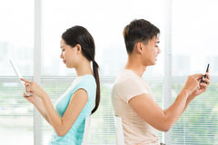 Gadgets are everywhere. Image of a young couple sitting and networking with their gadgets stock images