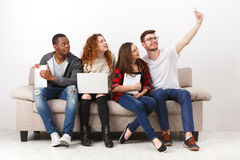 Gadgets, selfie, friends having fun together. Capturing happy moments. Young friends making selfie while sitting together on couch and using gadgets Royalty Free Stock Images