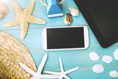 Gadgets on the Table with Starfish, Shells and Hat Stock Images