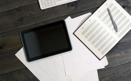 Gadgets on the wooden table. Computer tablet documents. Royalty Free Stock Photo