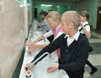 Students wash their hands before entering the dining room stock image