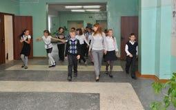 The teacher walks with the children along the school corridor stock photography