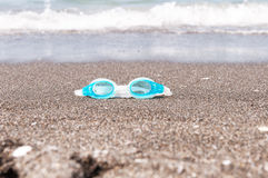 Gafas de la nadada en la arena Foto de archivo