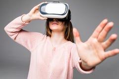 Gafas de la visión de la realidad virtual de las auriculares VR de la mujer que llevan atractiva joven que miran haber sorprendid Imágenes de archivo libres de regalías