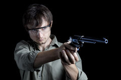 Gafas de seguridad del hombre que desgastan que apuntan la pistola Fotos de archivo libres de regalías