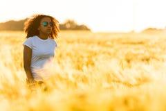 Gafas de sol adolescentes de la muchacha afroamericana de la raza mixta que colocan trigo Foto de archivo
