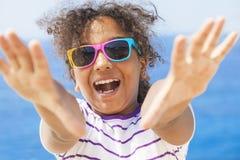 Gafas de sol afroamericanas de risa del niño de la muchacha de la raza mixta Imagenes de archivo