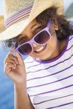 Gafas de sol afroamericanas y sombrero del niño de la muchacha de la raza mixta feliz Fotografía de archivo