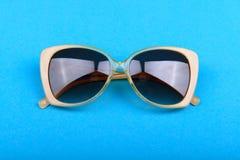 Gafas de sol amarillas en un fondo azul Fotografía de archivo
