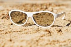 Gafas de sol blancas en la arena El concepto para el diseño del día de fiesta, verano Foto de archivo