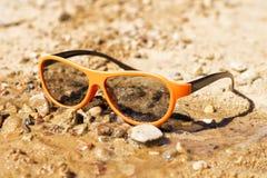 Gafas de sol blancas en la arena El concepto para el diseño del día de fiesta, verano Fotografía de archivo