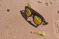 Gafas de sol brillantes del color oro en la arena Foto de archivo