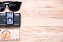 Gafas de sol, cámara del vintage y un compás a la izquierda en una luz Fotos de archivo libres de regalías