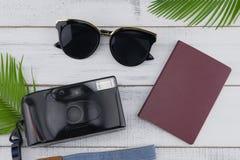 Gafas de sol, cámara de la película y pasaporte con las hojas del helecho imagen de archivo libre de regalías