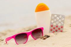 Gafas de sol, cáscaras, loción y píldoras rosadas de la vitamina E, concepto estacional fotos de archivo libres de regalías