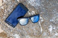 Gafas de sol con el móvil Foto de archivo libre de regalías