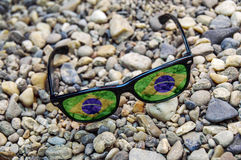 Gafas de sol con la reflexión de la bandera del Brasil en una costa Fotografía de archivo libre de regalías
