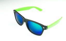 Gafas de sol con las lentes azules en el fondo blanco Foto de archivo