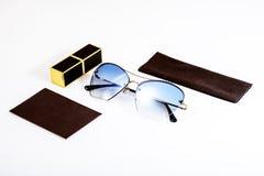 Gafas de sol con las lentes azules en una composición con un paño marrón en un fondo blanco fotografía de archivo