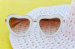 Gafas de sol de la moda en forma de corazón en el sombrero rosado Imagenes de archivo