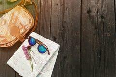 Gafas de sol elegantes del bolso del inconformista con los wildflowers púrpuras en mapa encendido Fotos de archivo