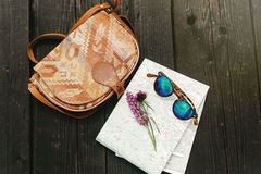 Gafas de sol elegantes del bolso del inconformista con los wildflowers púrpuras en mapa encendido Foto de archivo libre de regalías
