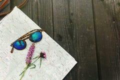 Gafas de sol elegantes del inconformista con los wildflowers púrpuras en mapa en bla Foto de archivo