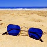 Gafas de sol en forma de corazón en la arena de una playa Fotografía de archivo