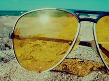 Gafas de sol en la arena cerca de un mar imagen de archivo libre de regalías